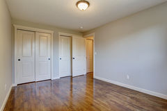 Simplistic hardwood bedroom. Simplistic hardwood bedroom with great lighting and two closets Royalty Free Stock Images