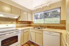 Simplistic kitchen room interior with beige cabinets and tile. Simplistic kitchen room interior with beige cabinets and brown tile Stock Photo