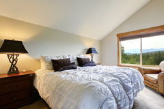 Simplistic master bedroom with grey bedding, black nightstands and mountain view. Stock Photo