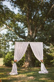 Simplistic wedding ceremony altar. Set up with big oak tree Stock Photos