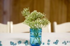 Simplistic White and Blue Table Arrangement - Wedding/Event Decor. Simplistic flower detail for wedding or event tables: Simplicity is trending with weddings and Royalty Free Stock Photos