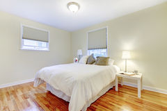 Simplistic white and brown bedroom interior with hardwood floor Stock Photos