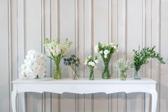 Simply composition of different white flower in vase on white vintage table.  royalty free stock photos