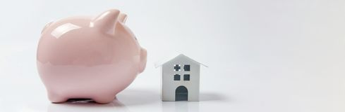 Miniature white toy house and piggy bank on white background royalty free stock photography