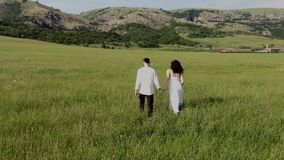 Simply dressed man and woman hold the hands and walk thru the green field near the farm with mountain range at the