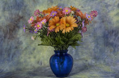 Simply flowers. Assorted flower in a small vase with a texture back ground Stock Images