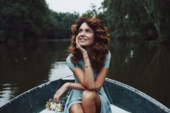 Simply happy. Beautiful young woman in elegant dress looking away and smiling while sitting in the boat royalty free stock images