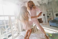 Simply happy. Cute little girl jumping on the bed with her mother while spending time at home stock photos