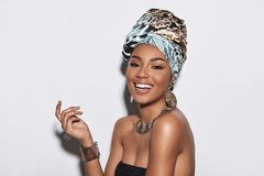 Simply happy. Attractive young African woman in turban looking at camera and smiling while standing against grey background royalty free stock photography