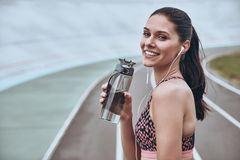 Simply happy. Beautiful young woman in sports clothing smiling and looking a camera while exercising outdoors royalty free stock images