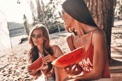 Simply happy. Two attractive young women smiling and eating watermelon while sitting on the beach royalty free stock photos