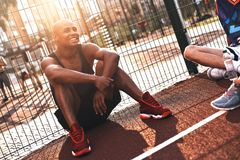 Simply happy. Young African man in sports clothing smiling while sitting on the basketball field outdoors royalty free stock photography