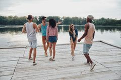 Simply having fun. Full length of happy young people in casual wear smiling and gesturing while enjoying beach party royalty free stock photography