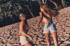 Simply having fun. Two attractive young women in shorts and swimwear smiling while running on the beach royalty free stock image