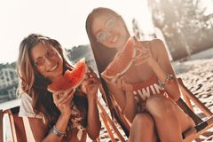 Simply having fun. Two attractive young women smiling and eating watermelon while sitting on the beach stock image
