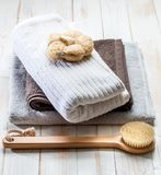 Simply healthy dry brushing and sustainable body care concept. With natural loofah, body brush or cotton towels over clean wooden background, top view royalty free stock image