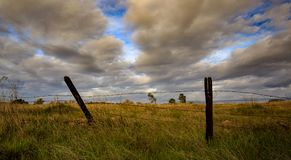 A simply pen space field with clouds rolling over fenced in. stock image
