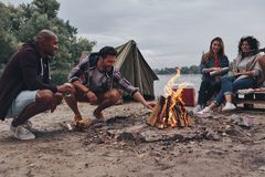 Simply relaxing. Group of young people in casual wear smiling while enjoying beach party near the campfire royalty free stock image