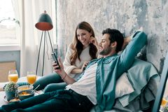 Simply resting. Beautiful young couple having breakfast while spending time in bed at home stock photo