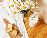 Simply stylish wooden kitchen with bottle of milk and glass on table, summer flowers camomile, healthy food moring Stock Photo