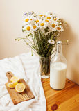 Simply stylish wooden kitchen with bottle of milk and glass on table, summer flowers camomile, healthy food moring Royalty Free Stock Image