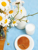 Simply stylish wooden kitchen with bottle of milk and glass on table, summer flowers camomile, healthy food morning Royalty Free Stock Photography