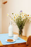 Simply stylish wooden kitchen with bottle of milk and glass on table, summer flowers camomile, healthy foog moring Royalty Free Stock Photos