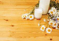 Simply stylish wooden kitchen with bottle of milk and glass on table, summer flowers camomile, healthy foog moring Royalty Free Stock Photography