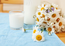 Simply stylish wooden kitchen with bottle of milk and glass on table, summer flowers camomile, healthy foog moring Stock Image
