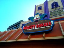 The Simpsons Krusty Burger sign with Springfield Elementary. School and Sideshow Bob behind it at Universal Studios, CA Stock Image