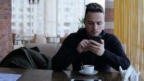 Simsen des gutaussehenden Mannes, sms auf Smartphone im Café sendend stock footage