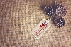 Simsen Sie frohe Feiertage geschrieben auf Aufkleber auf Naturfarbgewebehintergrund Kiefernkegel in einer Ecke mit der Kopie gesp Stockfotografie