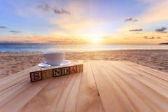 Simsen Sie hölzernen Block und Kaffeetasse auf hölzerner Tabelle Stockbild