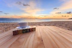 simsen Sie hölzernen Block und Kaffeetasse auf hölzerner Tabelle am Sonnenuntergang oder am Sonnenaufgangstrand Stockfotografie