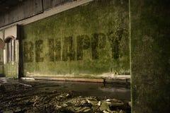 Simsen Sie ist glücklich auf der schmutzigen Wand in einem verlassenen ruinierten Haus Stockfoto