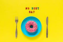 Simsen Sie KEINEN DIÄT-TAG, rosa Donut auf Platte und Tischbestecktafelmessergabel Konzept international kein Diät-Tag, am 6. Mai stockfotos