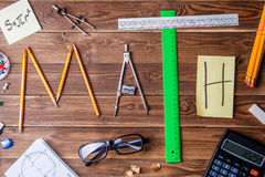 Simsen Sie Mathe, das aus Bleistiften, Machthabern, Rundschreiben, Bleistiftspitzer und Aufkleber mit dem Buchstaben besteht Stockbild
