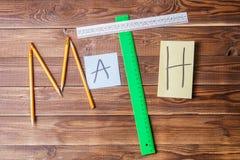 Simsen Sie Mathe, das aus Bleistiften, Machthabern, Rundschreiben, Bleistiftspitzer und Aufkleber mit dem Buchstaben besteht Lizenzfreie Stockfotografie