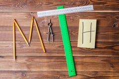 Simsen Sie Mathe, das aus Bleistiften, Machthabern, Rundschreiben, Bleistiftspitzer und Aufkleber mit dem Buchstaben besteht Stockfotografie