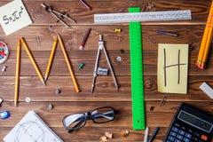 Simsen Sie Mathe, das aus Bleistiften, Machthabern, Rundschreiben, Bleistiftspitzer und Aufkleber mit dem Buchstaben besteht Stockbilder