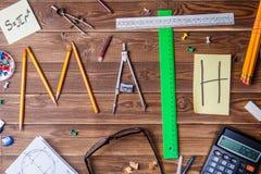 Simsen Sie Mathe, das aus Bleistiften, Machthabern, Rundschreiben, Bleistiftspitzer und Aufkleber mit dem Buchstaben besteht Lizenzfreies Stockbild
