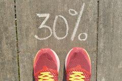 Simsen Sie 30 Prozent, die auf graue Pflasterung mit den Frauenbeinen in Turnschuhe, Ansicht von oben geschrieben werden lizenzfreie stockfotos