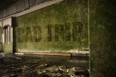 Simsen Sie schlechte Reise auf der schmutzigen Wand in einem verlassenen ruinierten Haus Stockbild