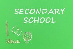 Simsen Sie Sekundärschule, hölzerne Miniaturen des Schulbedarfs auf grünem Hintergrund stockfotos