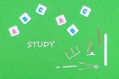 Simsen Sie Studie, von oben genanntem hölzernem minitures Schulbedarf und von ABC-Buchstaben auf grünem Hintergrund stockfotografie