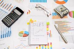 Simsen Sie Verkäufe am Notizbuch mit analytischen Diagrammen und Diagrammen Stockfotos