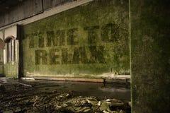 Simsen Sie Zeit, sich auf der schmutzigen Wand in einem verlassenen ruinierten Haus zu entspannen Lizenzfreie Stockfotos