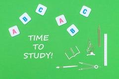 Simsen Sie Zeit, von oben genanntem hölzernem minitures Schulbedarf und von ABC-Buchstaben auf grünem Hintergrund zu studieren stockfoto