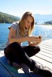 Simsende Mitteilung glücklicher blonder Dame mit mittlerem Schuss des Handys Lizenzfreie Stockbilder