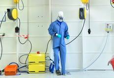 Simulacre dans le masque respiratoire et uniforme dans le secteur pour la coloration de voiture photographie stock